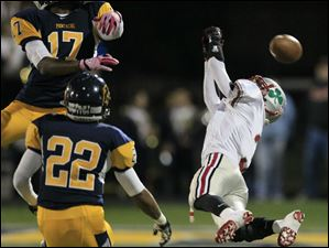 Whitmer player Mark Meyers, 17, and LeRoy Alexander, 22, defend as Central Catholic High School player Jake Garcia, 3, can't make the catch.