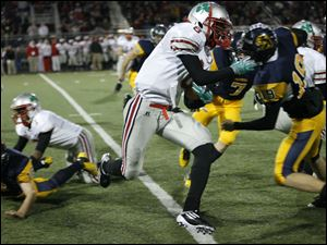 Central Catholic player Jayme Thompson, 8, tries to find running room as he returns a kick in the first quarter.