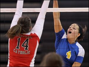 St. Ursula's Erin Williams (4) spikes the ball against Central Catholic's Olivia Pina (14) Saturday.