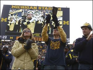 From left: Taylor Webb, of Flint, Mich., and Sylvania, Ohio residents David Wise and Jarman Davis cheer for the band before the start of the Purdue game at Michigan Stadium in Ann Arbor, Mich.