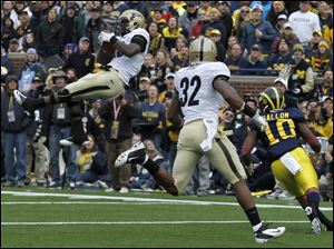 Purdue's Josh Johnson intercepts a pass intended for Jeremy Gallon (10) during the first half at Michigan Stadium in Ann Arbor, Mich. Albert Evans (32) runs on to the play.