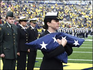 UM Navy ROTC member Brooke Schaffer carries the U.S. flag to the flagpole during first half at Michigan Stadium in Ann Arbor, Mich.