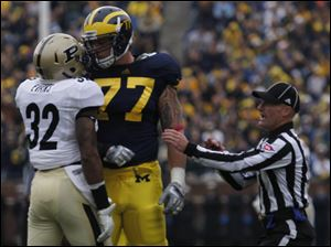 Purdue's Albert Evans and UM's Taylor Lewan get face to face during first half at Michigan Stadium in Ann Arbor, Mich.