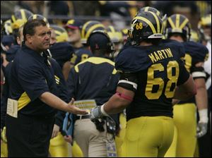 UM head coach Brady Hoke shakes hands with Mike Martin after Martin forced a Purdue safety during first half at Michigan Stadium in Ann Arbor, Mich.