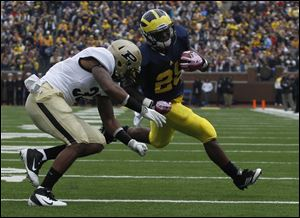 Purdue's Albert Evans covers UM's Fitzgerald Toussaint during first half at Michigan Stadium in Ann Arbor, Mich.