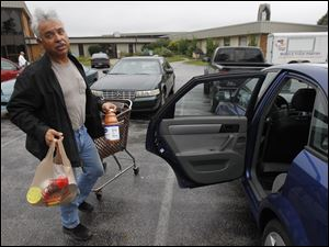 David Estrada returns to his car after receiving groceries from the Food for Thought pantry in Oregon. He started going to the pantry more than a year ago.