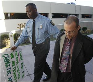 Police Sgt. Harold Mosley leads Occupy Toledo protestor Rick Van Landigham to the public safety building for booking.