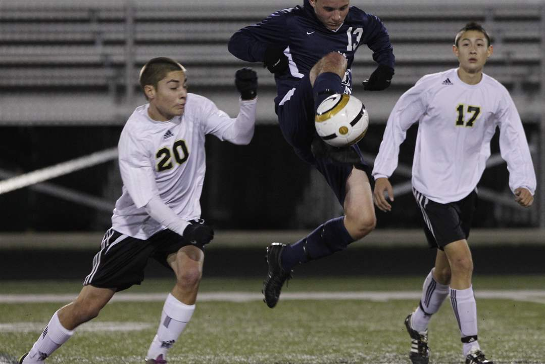 Perrysburg-s-Jamie-Gonzalez-left-and-Stephen-Beaujean-defend-St-John-s-Camden-Buescher