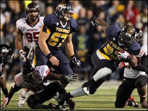 University of Toledo RB David Fluellen (22) runs the bal against Northern Illinois during the second quarter Tuesday.