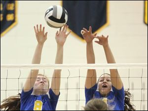 St. Ursula's Lauran Graves (8) and Erin Williams (4) block a spike from  Avon Lake's Christine Bohan (12) Wednesday during a Division I volleyball regional semifinal at Norwalk High School.
