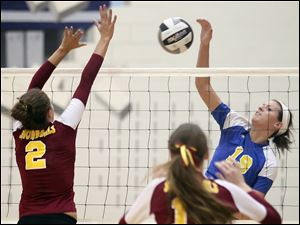 St. Ursula's Maddie Burnham (19) spikes the ball against Avon Lake's Whitney Craigo (2) Wednesday during a Division I volleyball regional semifinal at Norwalk High School.