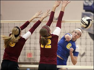 St. Ursula's Cassidy Croci (6) spikes the ball against Avon Lake's Lauren Bakaitis (3) and Christine Bohan (12) Wednesday during a Division I volleyball regional semifinal at Norwalk High School.
