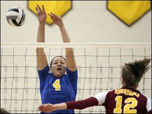 St. Ursula's Erin Williams (4) hits the ball against Avon Lake's  Christine Bohan (12) Wednesday during a Division I volleyball regional semifinal at Norwalk High School.