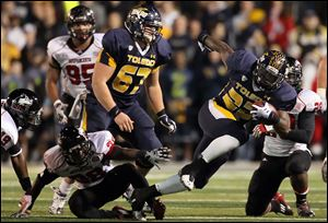 Toledo running back David Fluellen (22) runs the ball against Northern Illinois during the second quarter of an NCAA college football game at the Glass Bowl in Toledo.