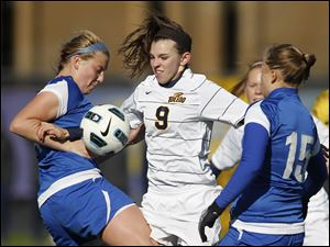 Toledo's Kirsten Catloth, 9, battles for the ball with Buffalo's Jackie Hall, left, and Karen McMahon, 15, right.