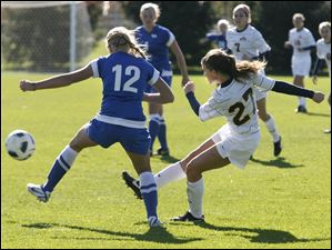 Toledo's Rachel MacLeod, 27, kicks a shot into the goal past Buffalo's Natalie Jurisevic, 12, during the second half.