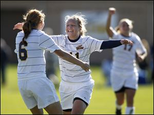 Toledo's Nicole Gyurgyik, 11, center, celebrates her goal with teammate Kristen Lynn, 6, during the second half of their MAC women's soccer semifinal game.