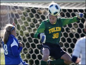Toledo goal keeper Vicki Traven blocks a shot by Buffalo's Katie Roberts, 8, left.