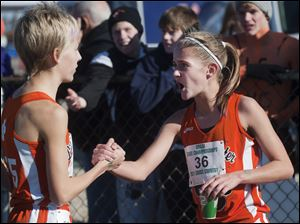 Liberty Center High School runner Brittany Atkinson (36) greets teammate Kelly Haubert after finishing the Girl's Div. II State High School Cross Country Championship in Hebron. Atkinson won the race as did the Liberty Center team.