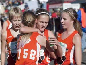 Liberty Center runners Brittany Atkinson, center, gets a hug from teammate Paige Chamberlain (752) as Kelly Haubert, left, and Chelsea Knapp, right, stand by after finishing the Girl's Div. III State High School Cross Country Championship in Hebron.