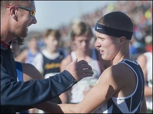 Napoleon High School runner Steve Weaver is greeted by assistant coach Jeff Ressler after Weaver's win in the Boy's Div. II State High School Cross Country Championship in Hebron.