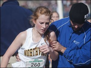 Sylvania Northview High School runner Maureen Dean gets a hand from an official after finishing the Girl's Div. II State High School Cross Country Championship in Hebron.