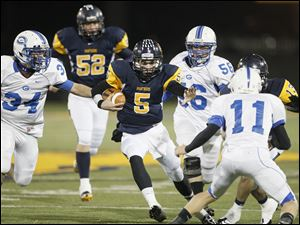 Whitmer quarterback Tyler Palka cuts between Anthony Wayne's Hunter Lonseth, left, Todd Bernhard, and Josh Schwerer in last night's Division I playoff game at Whitmer.