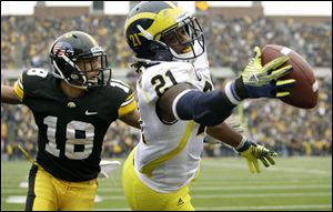 Michigan's Junior Hemingway tries to catch a pass in front of Iowa cornerback Micah Hyde in the end zone during the final seconds on Saturday. The officials said he never got control. UM players disagree.  associated press