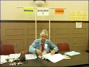 Barbara Steagall works Tuesday at a polling locaiton inside the Maumee Branch Library.