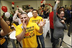 Toledo Fire Dept. Lt. Daniel Brown-Martinez, front left, his brother David Brown, center,and Rachael Lee of Toledo, right, join the crowd celebrating the defeat of State Issue 2 at the Teamsters Hall in Toledo.