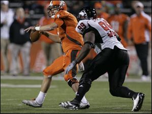 BGSU quarterback Matt Schilz is chased down by NIU's Mathew Sims.
