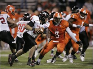 NIU quarterback Jordan Lynch runs with the ball during second half as BGSU's Kevin Moore pursues.