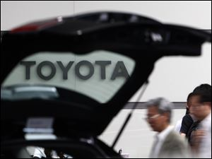 People walk by a car on display at Toyota's Tokyo, Japan, headquarters.