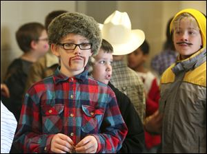 Ten-year-old Logan Moore wears a coon skin hat  and a mustache during Harvest Day at Wayne Trail School in Maumee.