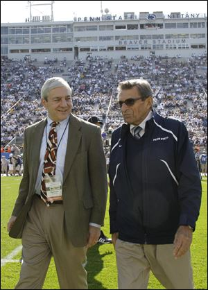 Penn State president Graham Spanier, left, and head football coach Joe Paterno chat before an NCAA college football game against Iowa in State College, Pa.