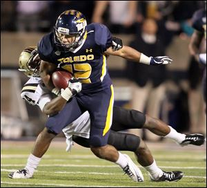 University of Toledo WR Eric Page runs the ball against  Western Michigan's Donald Celiscar (34) during the second quarter Tuesday.