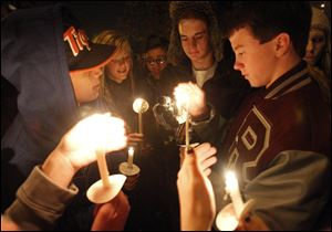 Students from left: A.J. Santellana, Lyndsey Skala, Noah Asmus, and C.J. Ball, light candles during a vigil for Rossford High School junior Kerry Keller who is battling cancer.