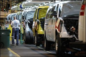 A General Motors employee works on a van assembly line at GM's plant in Wentzville, Mo.
