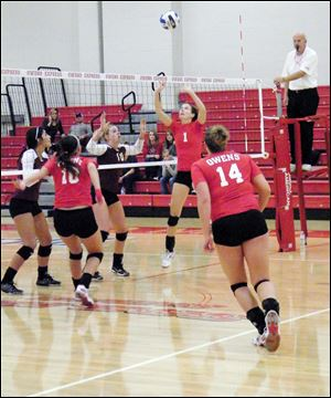 Molly Hilfinger, 1, sets the ball for teammate Julia Haupricht, 10, as Brittany Egbert, 14, runs in to assist.