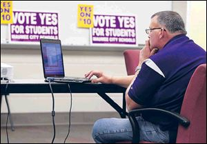 Paul Brotzki, treasurer of Maumee City Schools, monitors voting results.