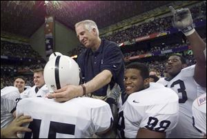 Then Penn State defensive coordinator Jerry Sandusky reaches out to defensive back Brandon Scott (45) as he is carried by players, including Jason Wallace (88), after they defeated Texas A&M in the Alamo Bowl, in San Antonio, Texas, in this Dec. 28, 1999, file photo.