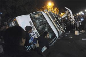 Penn State students flip a television news van during a riot Wednesday.