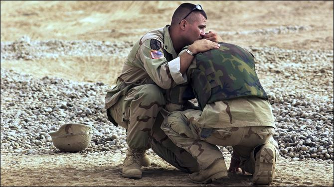 iraq hug toledo U.S. military police officer Brian Pacholski comforts his hometown friend, U.S. military police David Borell, both from Toledo, Ohio, at the entrance of the military base in Balad, about 50 kilometers (30 miles) northwest of Baghdad, Friday, June 13, 2003. Borell broke down after seeing three Iraqi children who were injured while playing with explosive material.