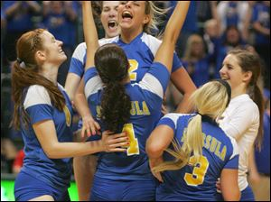 St. Ursula Academy's Madison Strall, center, leaps into her teammates after they won the semi-final game.