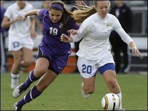 Toledo St. Ursula's Kelly Farell, right, and St. Francis DeSale's Maria Riley chase a loose ball during the first half of the OHSAA Div. II state soccer championship Saturday.