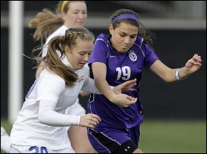 Toledo St. Ursula's Kelly Farell, left, and St. Francis DeSale's Maria Riley fight for a loose ball during the second half of the OHSAA Div. II state soccer championship Saturday.