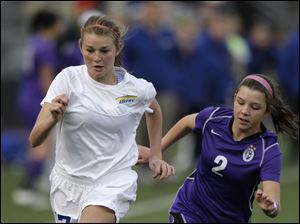 Toledo St. Ursula's Nicole Silverhart, left, dribbles the ball past St. Francis DeSales' Alexis Neri during the second half of the OHSAA Div. II state soccer championship Saturday.