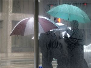 Three men covering themselves from the rain by umbrellas are reflected in a storefront on Adams Street.
