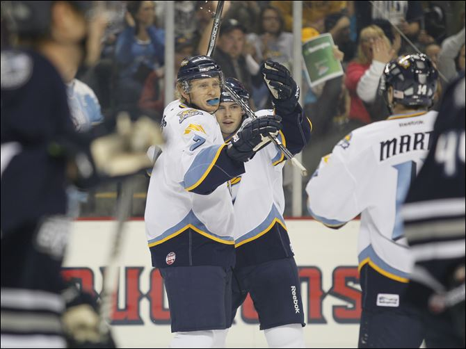 Bryan Rufenach (21) celebreate a goal Toledo Walleye players Kyle Rogers (17) left, and Bryan Rufenach (21) right, celebrate a first period goal by Rogers against the Chicago Express in an ECHL opener at Huntington Center, Saturday.