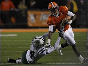 Ohio University's Omar Leftwich (4) dives at Bowling Green's Anthon Samuel (6) near the start of Wednesday's game at Doyt Perry Stadium.